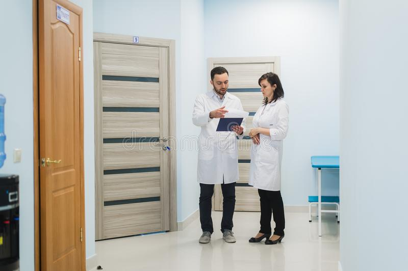 Two doctors discussing diagnosis while walking stock photos