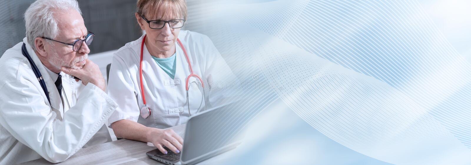 Two doctors discussing about medical report on laptop; panoramic banner royalty free stock images