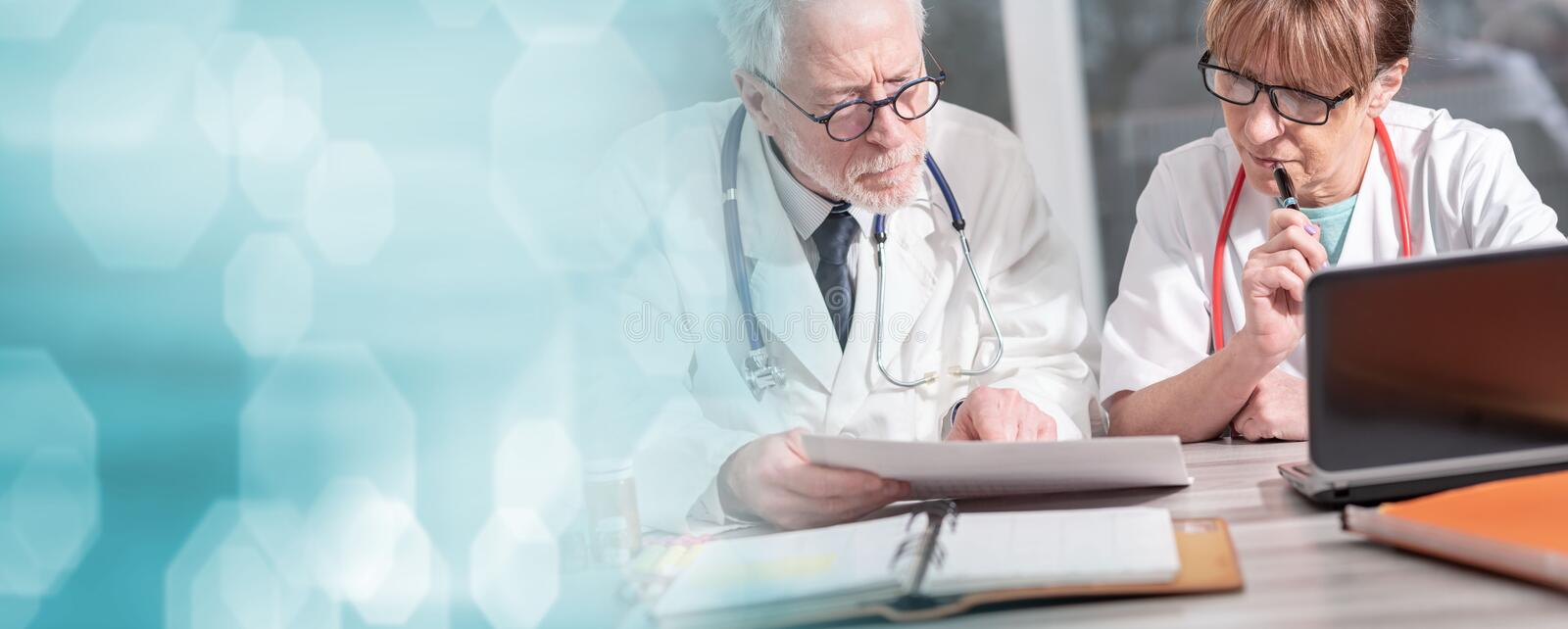 Two doctors discussing about medical results; panoramic banner royalty free stock images