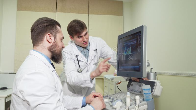 Two doctors discussing ultrasound scanning results of a patient royalty free stock images