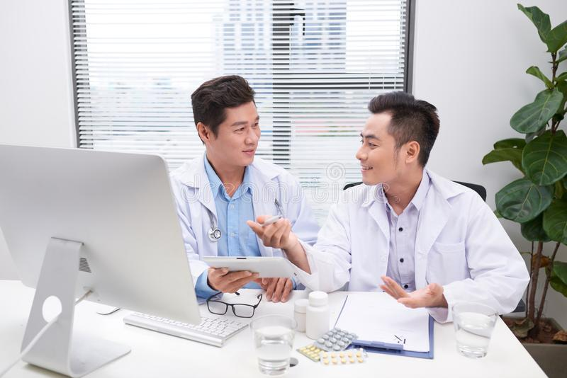 Two doctors holding and talking about patient on office stock image