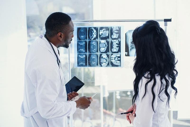 Two doctors look at an x-ray and discuss the problem. Medical technicians pointing at MRI x-ray of patient. Radiologist. Two doctors look at an x-ray and discuss royalty free stock photography