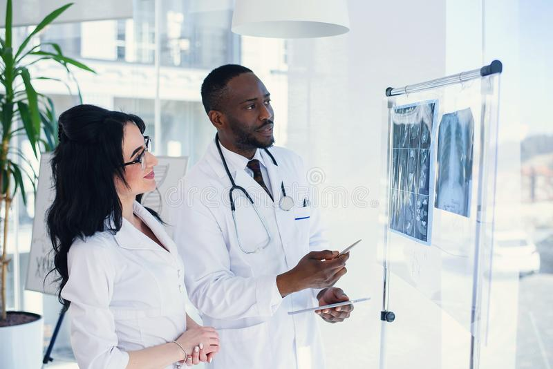 Two doctors look at an x-ray and discuss the problem. Medical technicians pointing at MRI x-ray of patient. Radiologist. Two doctors look at an x-ray and discuss stock photo
