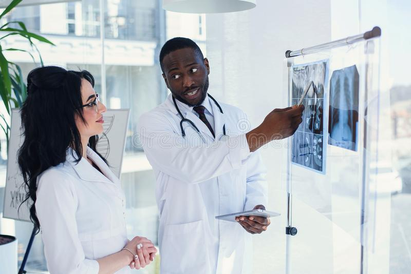 Two doctors look at an x-ray and discuss the problem. Medical technicians pointing at MRI x-ray of patient. Radiologist. Two doctors look at an x-ray and discuss stock image