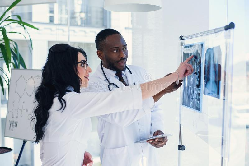 Two doctors look at an x-ray and discuss the problem. Medical technicians pointing at MRI x-ray of patient. Radiologist. Two doctors look at an x-ray and discuss royalty free stock images