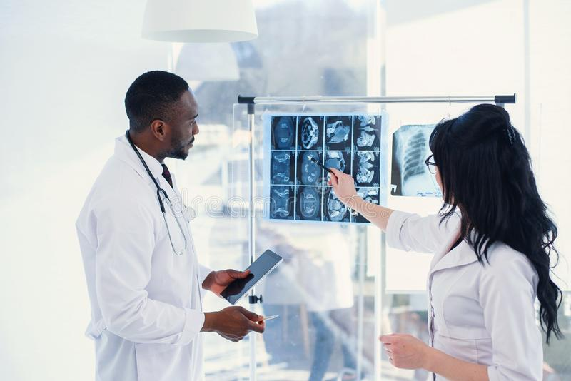 Two doctors look at an x-ray and discuss the problem. Medical technicians pointing at MRI x-ray of patient. Radiologist. Two doctors look at an x-ray and discuss royalty free stock photos