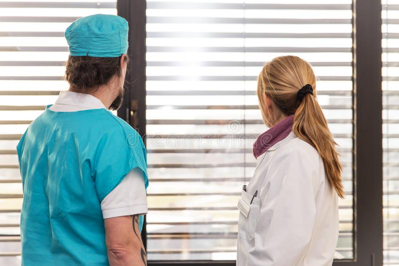 Two doctors or nurses in front of a window stock photos