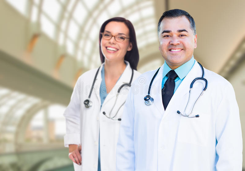 Two Doctors or Nurses Inside Hospital Building. Two Male and Female Doctors or Nurses Standing Inside Hospital Building stock photography