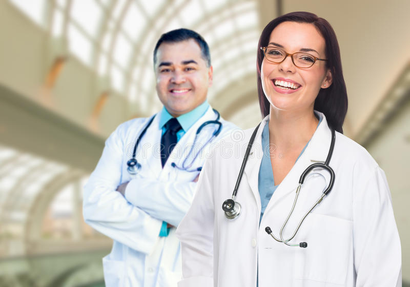 Two Doctors or Nurses Inside Hospital Building. Two Male and Female Doctors or Nurses Standing Inside Hospital Building stock images