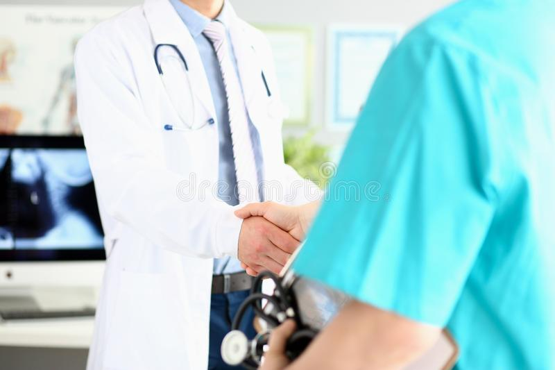 Two doctors in office shaking hands celebrating successful treatment stock photos