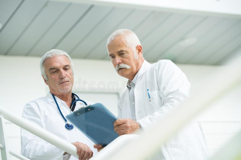 Two doctors talking as they walk through modern hospital. Doctor stock photos