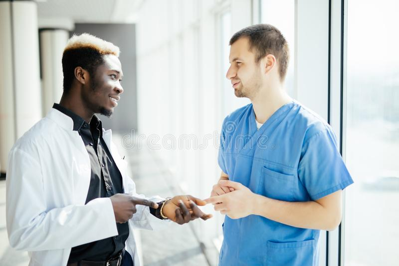 Mixed race Two Doctors Talking As They Walk Through Modern Hospital stock photography