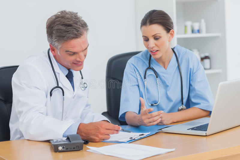 Two doctors working on an important folder. In a medical office royalty free stock photography