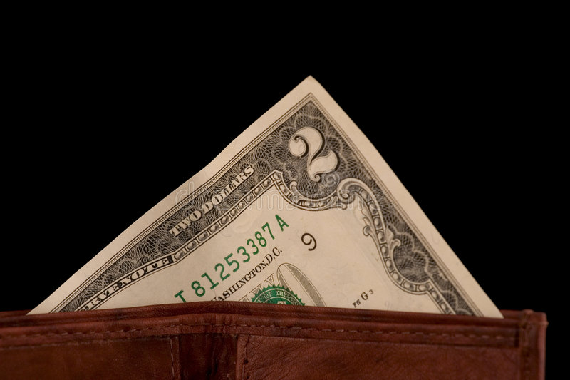 Two dollar bill. A two dollar bill sticking out of a wallet isolated on black stock images