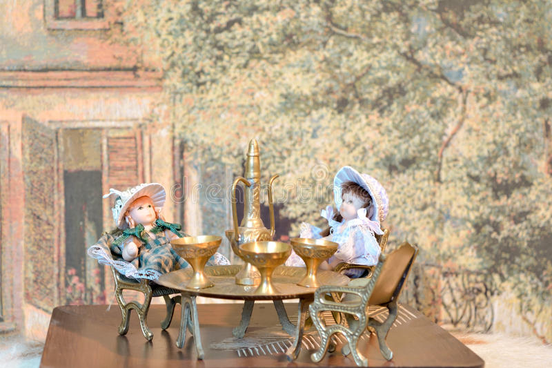 Decoration: two dolls having a tee party using oriental furniture against the tapestry royalty free stock image
