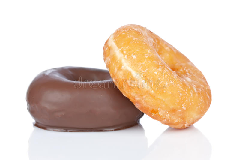 Two donuts. Two delicious donuts reflected on white background with shallow depth of field royalty free stock photo