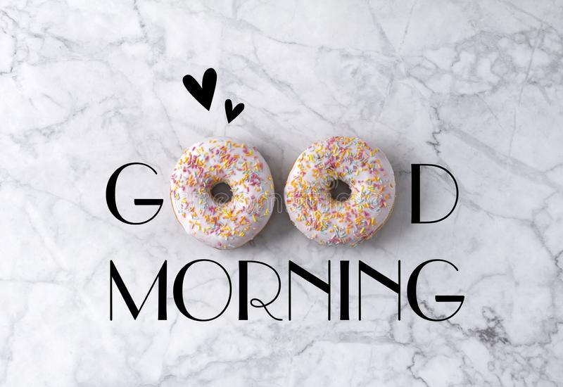 Two donuts and hearts. Good morning greeting written on marble gray background. Table top view stock image