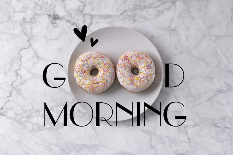 Two donuts and hearts. Good morning greeting written on marble gray background. Table top view stock photo