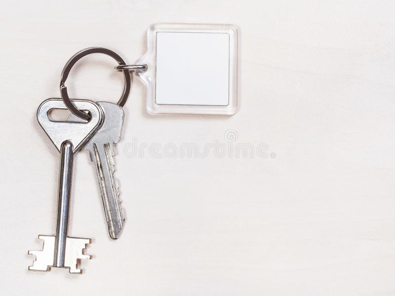 Two door keys on keyring with blank white keychain. On pale brown table royalty free stock photos