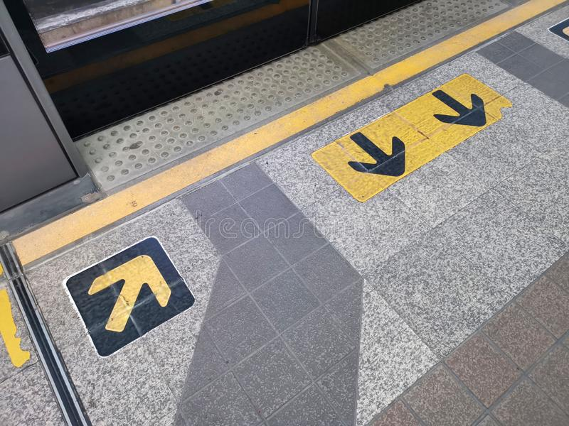 Two Down arrow direction stand up for the train, waiting for the train at platform behind yellow line for safety, Yellow line and. Yellow symbol, BTS sky train stock images