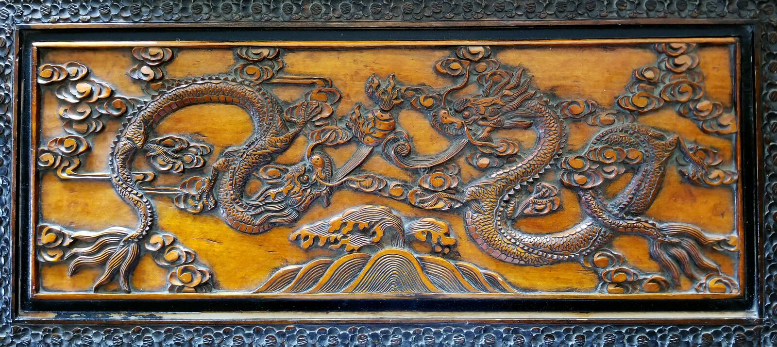 Two Dragons Dancing carved in camphor laurel wood. Two dragons carved in exquisite detail on lid of an antique hope chest made of camphor laurel wood orginially stock photo