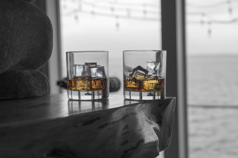 Two drams of whiskey on the rocks on fireplace mantel. Overlooking the sea on an overcast day stock photo
