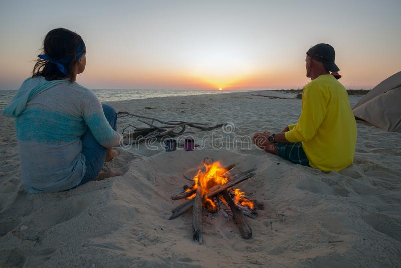 Two dreaming travelers are sitting next to a burning fire. On the beach and admiring setting sun over the sea. Amazing adventure in the wild. Wide angle, back royalty free stock photos