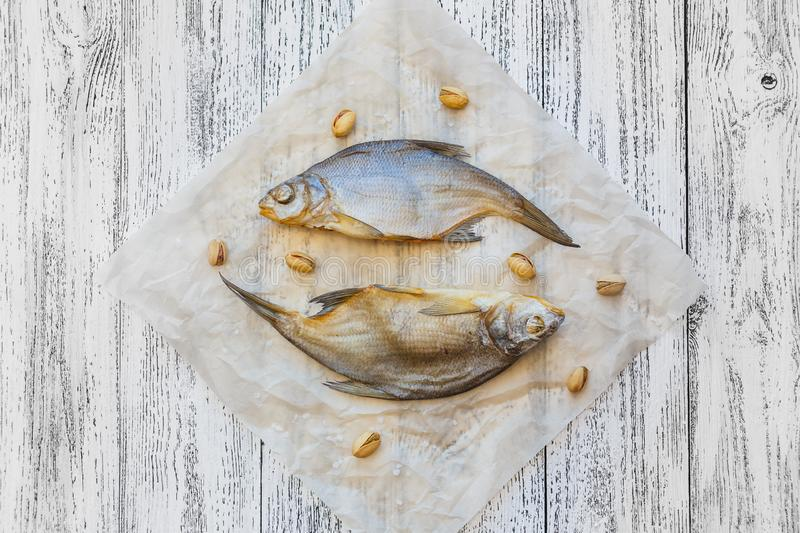 Two dried fish bream lie on a light wooden table stock photography