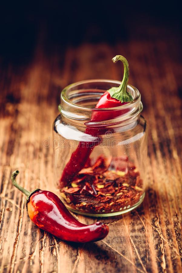 Two dried red chili peppers in jar stock image