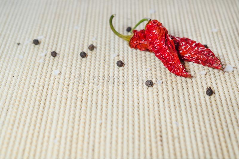 Two dried red hot pepper, sea salt and black peppercorns on a bamboo serviette. With copy space stock photography