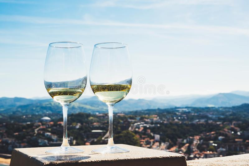 Two drink glass white wine standing on background blue sea top view city coast yacht from observation deck, romantic toast with al. Cohol panoramic cityscape royalty free stock photo