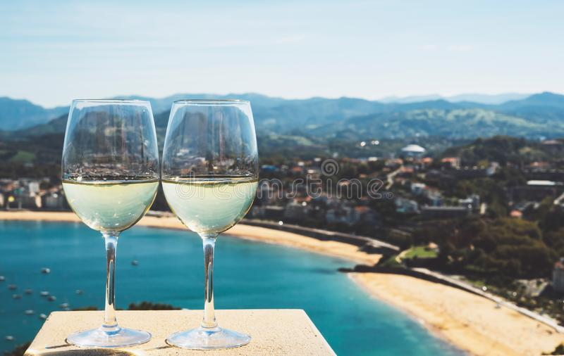 Two drink glass white wine standing on background blue sea top view city coast yacht from observation deck, romantic toast. With alcohol panoramic cityscape stock images