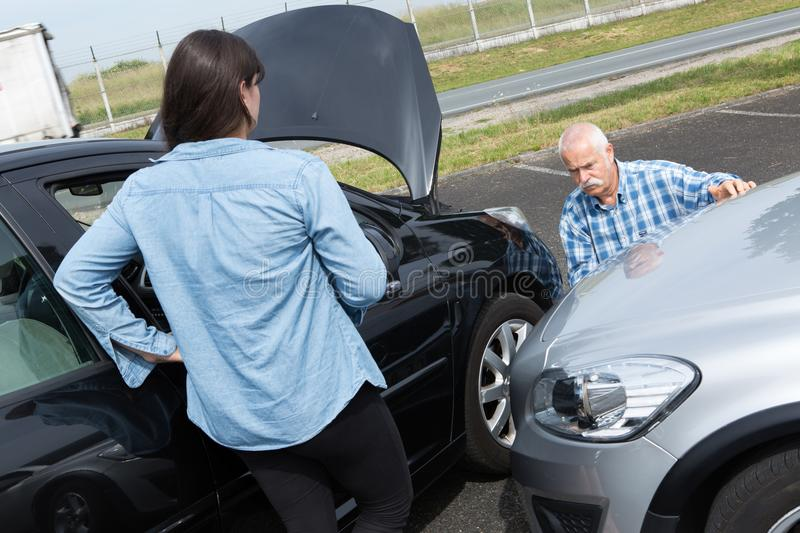 Two drivers arguing after traffic accident. Disappointment royalty free stock photo