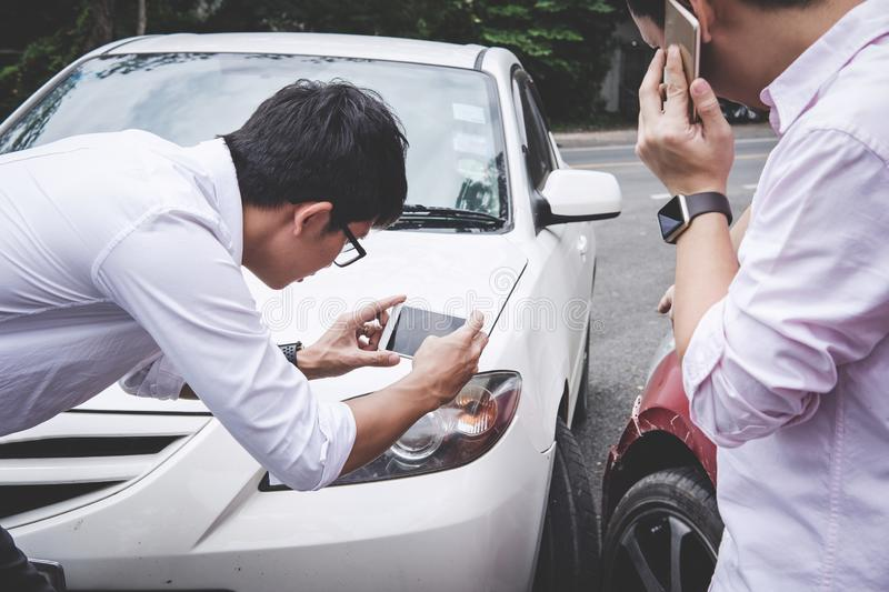 Two drivers man arguing after a car traffic accident collision and making phone call to Insurance Agent and take a photo, Traffic royalty free stock images