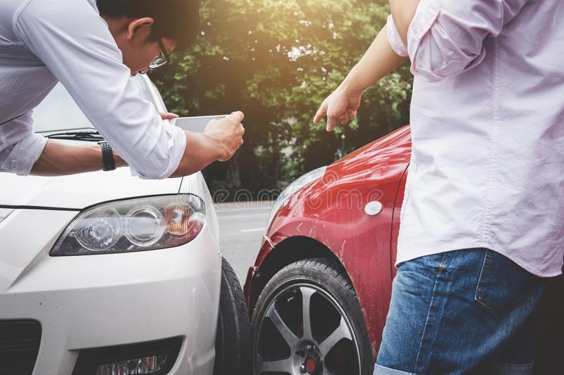 Two drivers man arguing after a car traffic accident collision a. Nd making phone call to Insurance Agent and take a photo, Traffic Accident and insurance royalty free stock photo