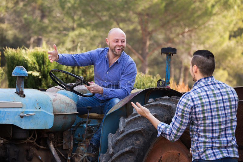 Two drivers working with tractor. Two positive male drivers working with tractor and chatting outdoor stock images