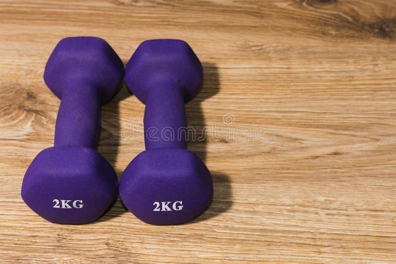 Two dumbbells of 2 kilograms on a wooden background stock image