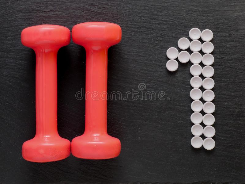 Two dumbbells and sign one made from medical pills. Sport and medicine goes together stock photo