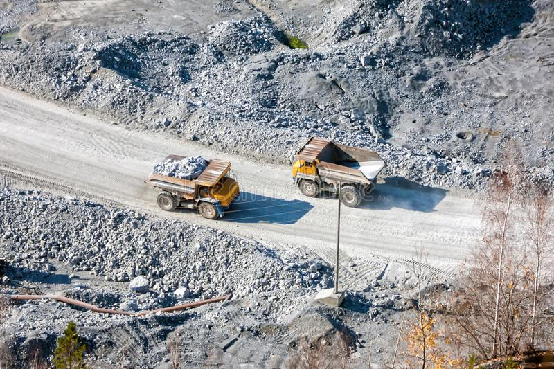 Two quarry dump trucks at the bottom of a stone pit royalty free stock photography