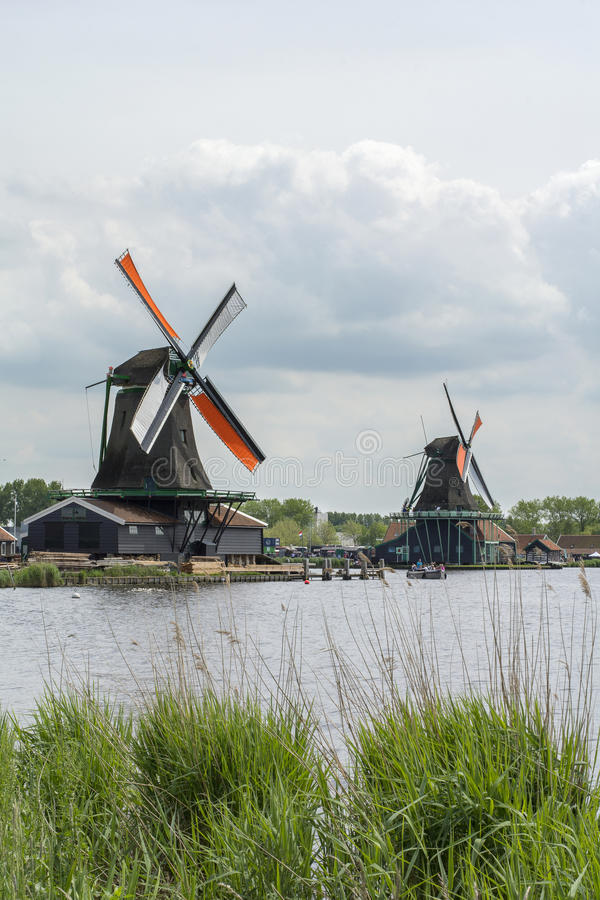 Two dutch mills with orange wings under the cloudy sky. In Zaanse Schans Netherlands stock images