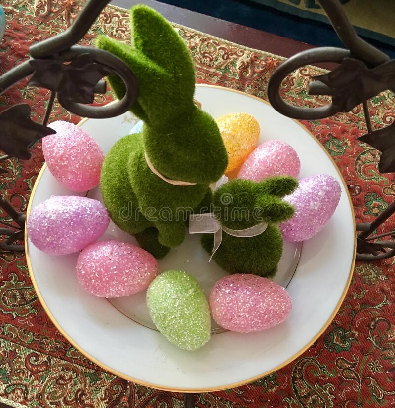 Green Easter Bunnies with Eggs. Two Easter Bunnies decorate a centerpiece with sparkly colored eggs of many pastel colors royalty free stock photography