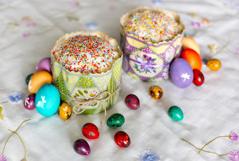 Two Easter cakes with sugar glaze and colorful - yellow, red, violet, green, violet - Easter eggs with white pictures stock photo