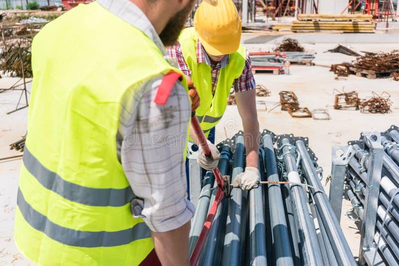 Two efficient blue-collar employees building a metallic scaffolding stock photos