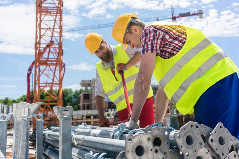 Two efficient blue-collar employees building a metallic scaffold royalty free stock photo