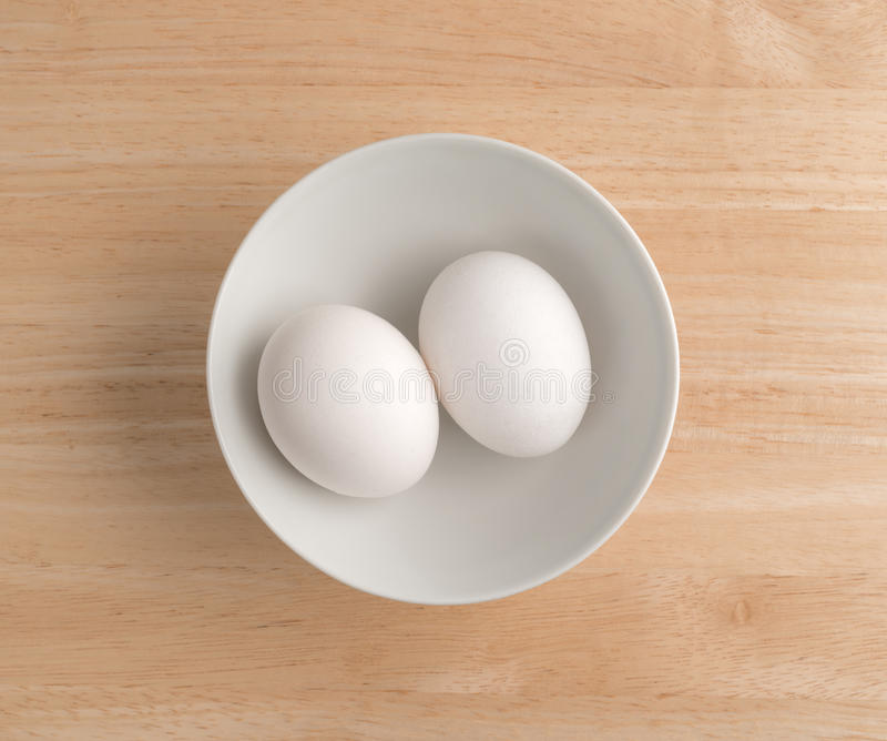 Two eggs in a bowl atop a wood table top. royalty free stock photo
