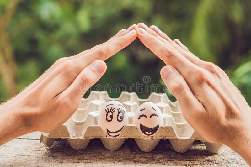 Two eggs - a married couple and two man`s open hands making a protection gesture Family life insurance, protecting family, family. Concepts royalty free stock photography