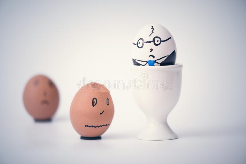 Two eggs white boss and black employee.  Racial discrimination on the workplace stock photos