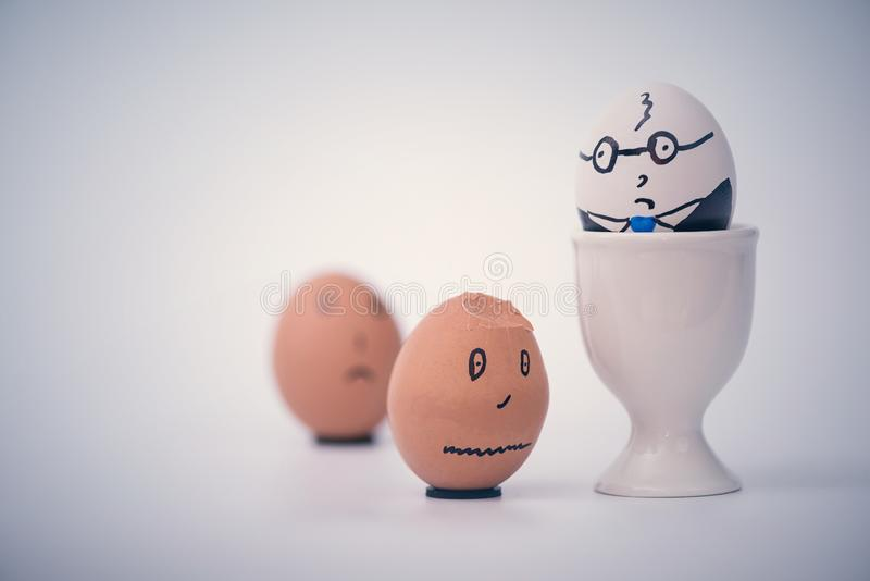 Two eggs white boss and black employee.  Racial discrimination on the workplace royalty free stock image