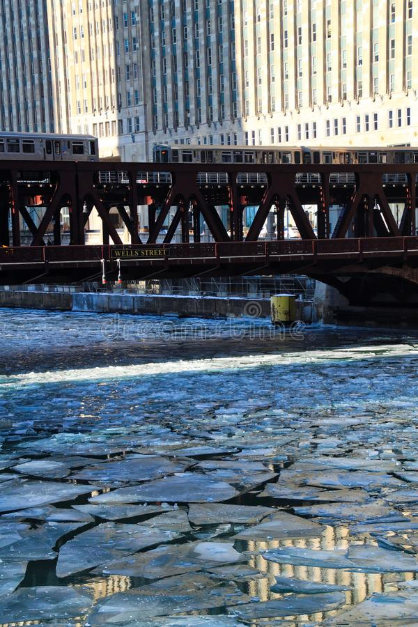 Two el trains travel over a blue and frozen Chicago River with ice chunks. stock image