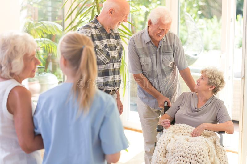 Men visiting sister. Two elder men visiting their disabled sister in wheelchair at the nursing house stock photo